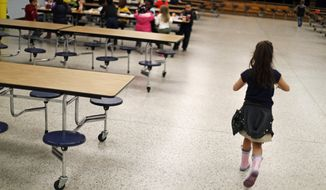 A student walks past empty seats in the Northside Elementary School cafeteria during lunchtime in Panama City, Fla., Thursday, Jan. 24, 2019. The county's student population has decreased by 14 percent since the storm, with some schools down by more than 40 percent. (AP Photo/David Goldman) ** FILE **