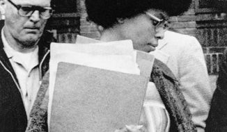 """FILE - In this April 25, 1977 file photo, Joanne Chesimard, member of the Black Panther Party and Black Liberation Army, leaves Middlesex County courthouse in New Brunswick, N.J. The New York Post reports that JetBlue removed a poster honoring Chesimard at New York's Kennedy Airport after being alerted via Twitter that she is """"a convicted cop killer."""" Now known as Assata Shakur, she escaped prison in 1979 and has been living in Cuba. (AP Photo, File)"""