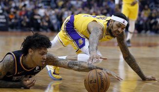Phoenix Suns forward Kelly Oubre Jr., left, dives for a loose ball in front of Los Angeles Lakers forward Brandon Ingram during the first half of an NBA basketball game Saturday, March 2, 2019, in Phoenix. (AP Photo/Rick Scuteri)