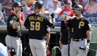 Pittsburgh Pirates' Jacob Stallings (58) is congratulated by Will Craig, left, and Lonnie Chisenhall (5) after hitting a two-run home run in the fifth inning during a spring training baseball game against the Philadelphia Phillies, Friday, March 1, 2019, in Clearwater, Fla. (AP Photo/Lynne Sladky)