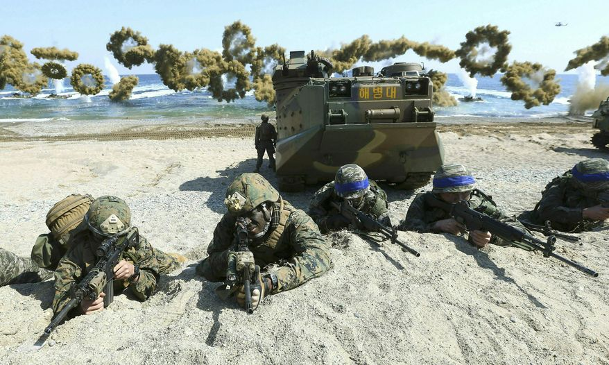 In this March 12, 2016, file photo, Marines of the U.S., left, and South Korea, wearing blue headbands on their helmets, take positions after landing on a beach during the joint military combined amphibious exercise, called Ssangyong, part of the Key Resolve and Foal Eagle military exercises, in Pohang, South Korea. (Kim Jun-bum/Yonhap via AP) ** FILE **