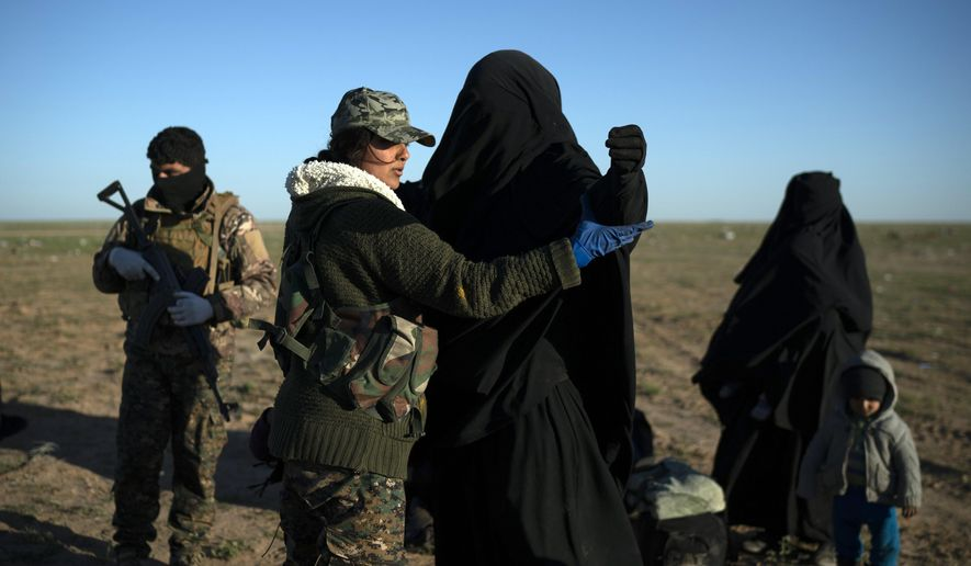 A woman is frisked by a U.S.-backed Syrian Democratic Forces (SDF) fighter at a screening area after being evacuated out of the last territory held by Islamic State militants, in the desert outside Baghouz, Syria, Friday, March 1, 2019. (AP Photo/Felipe Dana)