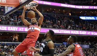 Washington Wizards forward Jabari Parker (12) dunks over Minnesota Timberwolves guard Josh Okogie (20) during the second half of an NBA basketball game, Sunday, March 3, 2019, in Washington. Also seen is Wizards center Thomas Bryant (13). The Wizards won 135-121. (AP Photo/Nick Wass) ** FILE **