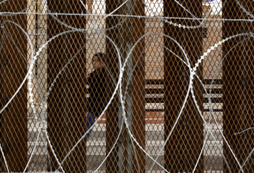 A woman waiting for a bus in Nogales, Mexico, is framed by a razor-wire-covered border wall separating it from Nogales, Ariz., Saturday, March 2, 2019. (AP Photo/Charlie Riedel)