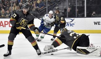 Vegas Golden Knights goaltender Marc-Andre Fleury (29) dives to block the puck with defenseman Shea Theodore (27) covering during the first period of an NHL hockey game against the Vancouver Canucks Sunday, March 3, 2019, in Las Vegas. (AP Photo/David Becker)