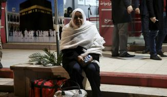 CORRECTION: IT IS THE UMRA, OR MINOR PILGRIMAGE, NOT THE HAJJ - A Palestinian Muslim pilgrim waits for a bus en route to the Rafah border between the Gaza Strip and Egypt before leaving for the umrah, or minor pilgrimage, to the holy city of Mecca, in Gaza City, Saturday, March 2, 2019. Gazan residents resumed the umrah pilgrimage, that can be undertaken at any time of the year, after nearly five years of an Egyptian ban. (AP Photo/Adel Hana)