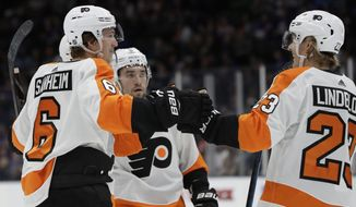 Philadelphia Flyers defenseman Travis Sanheim (6) celebrates with Flyers left wing Oskar Lindblom (23) as Flyers defenseman Robert Hagg, center, looks on after Sanheim scored the Flyers' second goal during the first period of an NHL hockey game, Sunday, March 3, 2019, in Uniondale, N.Y. (AP Photo/Kathy Willens)