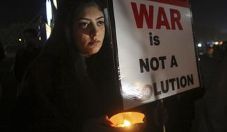 A member of the civil society group, Citizens of Lahore, participates in a candlelit vigil against war, in Lahore, Pakistan, Sunday, March 3, 2019. Residents near the disputed boundary in divided Kashmir region said Sunday it was quiet overnight, their first lull since a dangerous escalation between Pakistan and India erupted last week bringing the two nuclear-armed rivals close to full-out war. (AP Photo/K.M. Chaudary)