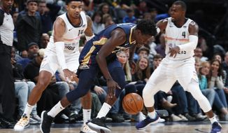 New Orleans Pelicans guard Jrue Holiday, center, drives past Denver Nuggets guard Gary Harris, left, and forward Paul Millsap on the way to scoring a basket during the second half of an NBA basketball game Saturday, March 2, 2019, in Denver. The Pelicans won 120-112. (AP Photo/David Zalubowski)