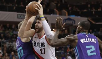 Portland Trail Blazers' Jusuf Nurkic (27) drives between Charlotte Hornets' Marvin Williams (2) and Cody Zeller (40) during the first half of an NBA basketball game in Charlotte, N.C., Sunday, March 3, 2019. (AP Photo/Chuck Burton)