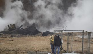 FILE - In this Jan. 17, 2019 file photo, staff from the Arkansas Department of Environmental Quality install a meteorological station to record wind speed and direction at the former stump dump site in Bella Vista, Ark. The underground fire at the illegal dumping site in northwest Arkansas has been smoldering for at least seven months, sending noxious smoke throughout the community, with costs to extinguish it estimated in the tens of millions. The fire, which started in July is beneath dozens of feet of waste and dirt in a former dump intended for tree limbs and stumps. (Ben Goff/The Northwest Arkansas Democrat-Gazette via AP, File)