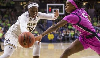 Notre Dame's Arike Ogunbowale (24) and Virginia's Khyasia Caldwell (5) compete for the ball during the first half of an NCAA college basketball game Sunday, March 3, 2019, in South Bend, Ind. (AP Photo/Robert Franklin)