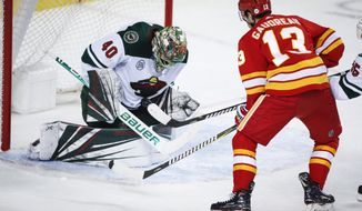 Minnesota Wild goalie Devan Dubnyk, left, stops a shot as Calgary Flames' Johnny Gaudreau watches during the first period of an NHL hockey game Saturday, March 2, 2019, in Calgary, Alberta. (Jeff McIntosh/The Canadian Press via AP)