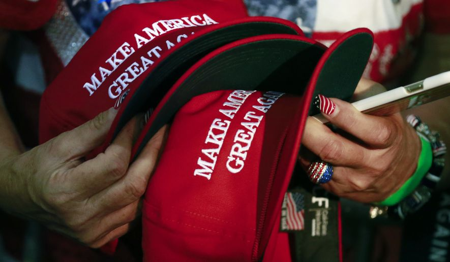 In this June 2, 2016, file photo, a woman holds hats to get them autographed by Republican presidential candidate Donald Trump during a rally in San Jose, Calif. (AP Photo/Jae C. Hong)