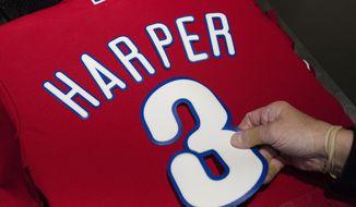 Peggy McBreen makes a Philadelphia Phillies' Bryce Harper baseball shirt at Citizens Bank Park in Philadelphia, Monday, March 4, 2019. (AP Photo/Matt Rourke) ** FILE **