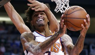 Phoenix Suns forward Kelly Oubre Jr. (3) is fouled by Milwaukee Bucks center Brook Lopez during the second half of an NBA basketball game, Monday, March 4, 2019, in Phoenix. (AP Photo/Matt York)