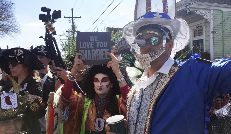 Costumed revelers gather Monday, March 4, 2019, for the annual Krewe of Red Beans march in New Orleans. The usually lighthearted parade began with a funeral dirge by a brass band in memory of Sharree Walls, a krewe member who was one of two killed when a car veered into a bike lane Saturday night. (AP Photo/Kevin McGill)
