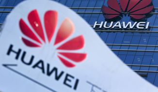 This Dec. 18, 2018, file photo, shows company signage on display near the Huawei office building at its research and development center in Dongguan, in south China's Guangdong province. China says the U.S. is using a double standard in claiming Chinese law requires telecoms giant Huawei to violate other countries' information security. (AP Photo/Andy Wong, File)