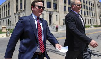 FILE - In this May 9, 2018, file photo, Sedgwick County Commissioner and former state senator Michael O'Donnell, left, leaves the federal courthouse in Wichita, Kan. The former Kansas legislator accused of fraudulently taking $10,500 from campaign funds for his personal use took the stand Thursday, Feb. 28, 2019, to defend himself in his federal trial on 23 counts of wire fraud and three counts of money laundering related to his state and county campaign funds. (Travis Heying/The Wichita Eagle via AP, File)
