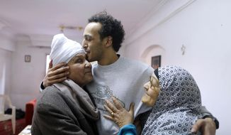 Mahmoud Abu Zaid, a photojournalist known as Shawkan, center, is hugged by his parents at his home in Cairo, Egypt, Monday, March 4, 2019. Shawkan was released after after five years in prison. (AP Photo/Amr Nabil)