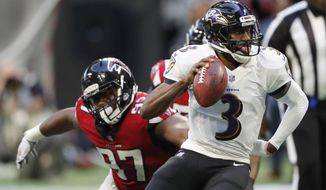 In this Dec. 2, 2018, photo, Baltimore Ravens quarterback Robert Griffin III (3) runs out of the pocket as Atlanta Falcons defensive tackle Grady Jarrett (97) defends during the second half of an NFL football game in Atlanta. (AP Photo/John Bazemore) **FILE**
