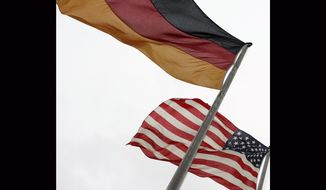 FILE - In this Feb. 22, 2005 file photo, German and US flags flap in the wind in front of the castle in Mainz, Germany, ahead of the meeting between US President George W. Bush and German Chancellor Gerhard Schroeder will meet here. A new survey released Monday March 4, 2019, shows Americans and Germans differ widely on their assessments of the state of relations between the two countries, but hold very similar views on international issues, including their support for NATO. (AP Photo/Markus Schreiber, File)