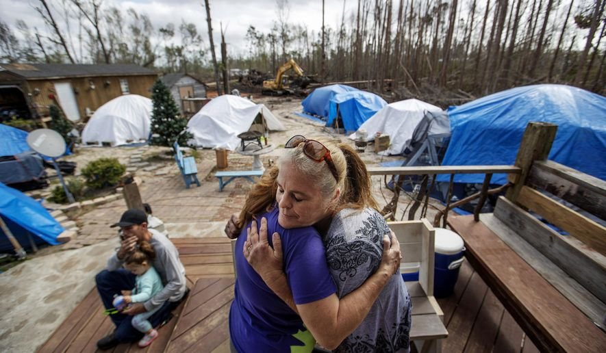 "Diahnn ""Shelly"" Summers, right, embraces Lori Hogan, who is currently living in a tent in Summers' backyard months after Hurricane Michael hit in Youngstown, Fla, Wednesday, Jan. 23, 2019. ""This is the first time I've felt comfortable since the hurricane,"" said Hogan. ""This is home for me and I love it."" A small village has popped up in Summers' backyard outside Panama City: Where there once was an empty grassy space, tents now form a circle around a fir tree with Christmas lights. The tents are currently home for local residents who are still homeless months after Hurricane Michael screamed ashore with 155-mph winds, flattening, blowing away or rendering uninhabitable thousands of houses. (AP Photo/David Goldman)"