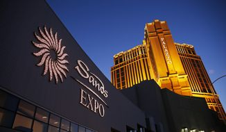 FILE - This June 17, 2014 file photo shows the Sands Expo and Convention Center and The Palazzo in Las Vegas. The properties are owned and operated by Las Vegas Sands Corp. Jury selection has begun for a trial to determine how much casino corporation Las Vegas Sands Corp. has to pay to a Hong Kong businessman who helped the company open its first resort in the Chinese gambling enclave of Macau. A judge and attorneys for Richard Suen and Sands told about 50 prospective jurors on Monday, March 4, 2019, that a panel of 15 will begin hearing the case March 11. (AP Photo/John Locher, File)