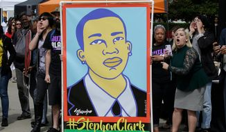 In this April 9, 2018, file photo protesters display an image of Stephon Clark at a crime victims rights rally, at the Capitol in Sacramento, Calif. Two Sacramento police officers won't face criminal charges for the fatal shooting of Clark following a chase that ended in his grandparents' yard and started a series of angry protests that roiled California's capital city, the county's top prosecutor announced Saturday, March 2, 2019, following a nearly yearlong investigation. (AP Photo/Rich Pedroncelli, File)