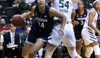 Connecticut's Napheesa Collier looks for the basket as she moves past South Florida's Alyssa Rader (54) during the first half of an NCAA basketball game Monday, March 4, 2019, in Tampa, Fla. (AP Photo/Steve Nesius)