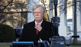 National Security Adviser John Bolton straightens his tie before an interview, Tuesday, March 5, 2019, at the White House in Washington. (AP Photo/Jacquelyn Martin)