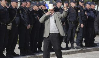 A protester flashes the victory sign in front of Albanian policemen guarding the parliament building as opposition supporters gather to take part in an anti-government rally , in Tirana , Albania, Tuesday, March 5, 2019. The opposition demanded the government step down, claiming it's corrupt and has links to organized crime. (AP Photo/ Hektor Pustina)