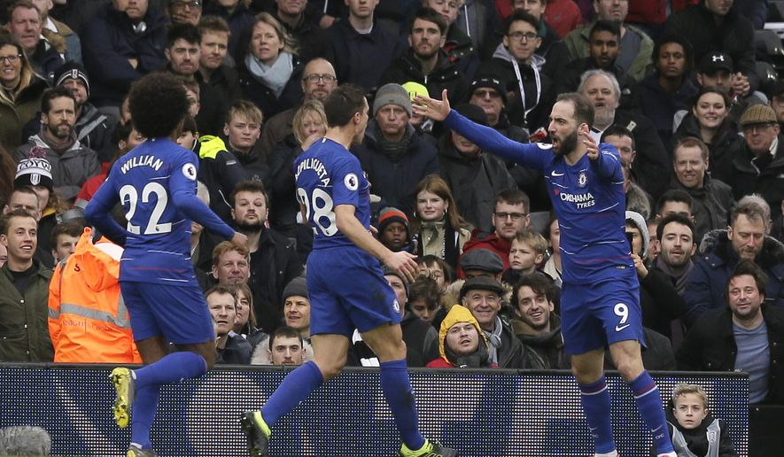 Chelsea's Gonzalo Higuain, right, celebrates with his teammates Cesar Azpilicueta, center and Willian, after scoring his side's opening goal, during the English Premier League soccer match between Fulham and Chelsea at Craven Cottage stadium in London, England, Sunday, March 3, 2019. (AP Photo/Tim Ireland)