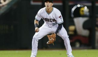 FILE - In this July 20, 2018, file photo, Arizona Diamondback' Jake Lamb plays third base against the Colorado Rockies during a baseball game in Phoenix. Lamb is taking over at first base for the Diamondbacks, replacing Paul Goldschmidt, who was traded to the St. Louis Cardinals in December.  (AP Photo/Darryl Webb, File)