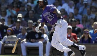 Colorado Rockies' Ian Desmond hits an RBI-single against the San Francisco Giants during the first inning of a spring baseball game in Scottsdale, Ariz., Sunday, March 3, 2019. (AP Photo/Chris Carlson)