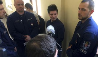 Portuguese Rui Pinto, center, is surrounded by police officers in the hallway of the Metropolitan Court in Budapest, Hungary, Tuesday, March 5, 2019 as he awaits a decision on his extradition to Portugal. (AP Photo/Pablo Gorondi)