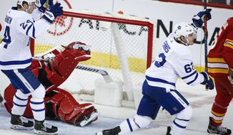 Toronto Maple Leafs' Tyler Ennis, right, celebrates his goal on Calgary Flames goalie David Rittich during first period NHL hockey action in Calgary, Alberta, Monday, March 4, 2019. (Jeff McIntosh/The Canadian Press via AP)