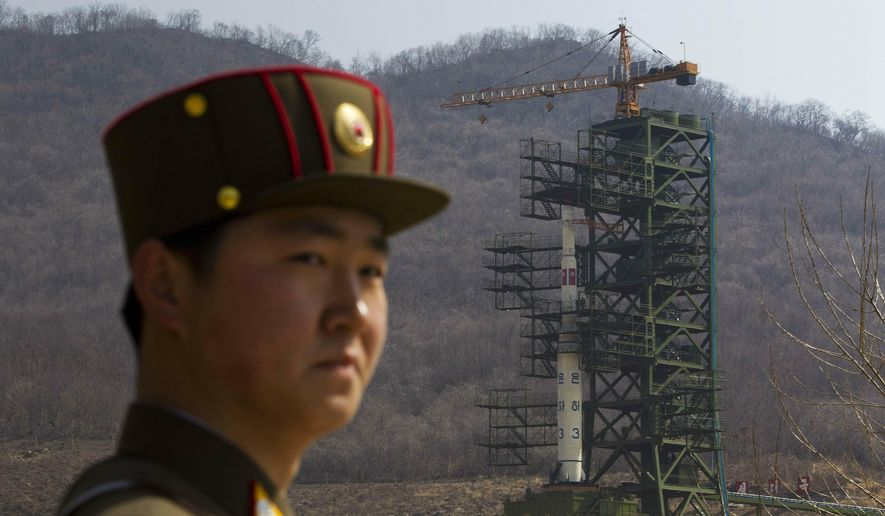 In this April 8, 2012, file photo, a soldier stands in front of the Unha-3 rocket at a launching site in Tongchang-ri, North Korea. North Korea is reportedly restoring facilities at its long-range rocket launch site that it had dismantled as part of disarmament steps last year. A major South Korean newspaper reports that the country's spy service gave such an assessment to lawmakers in a private briefing on Tuesday. (AP Photo/David Guttenfelder, File)