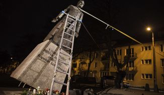 FILE - In this Thursday Feb. 21, 2019 file photo, activists in Poland pull down a statue of a prominent deceased priest, Father Henryk Jankowski, who allegedly abused minors sexually, in Gdansk, Poland. The new mayor of the Polish city of Gdansk, Aleksandra Dulkiewicz, said late Monday March 4, 2019, the statue of controversial Solidarity-era priest Henryk Jankowski, at the center of allegations he abused minors, should not stand in a public place. (AP Photo/Bartek Sabela/Gazeta Wyborcza, File)