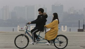 A couple wearing masks ride a bicycle as the cityscape is covered with a thick haze of fine dust particles in Seoul, South Korea, Tuesday, March 5, 2019. South Korean Environment Ministry issued emergency fine dust reduction measures on Tuesday. (AP Photo/Ahn Young-joon)