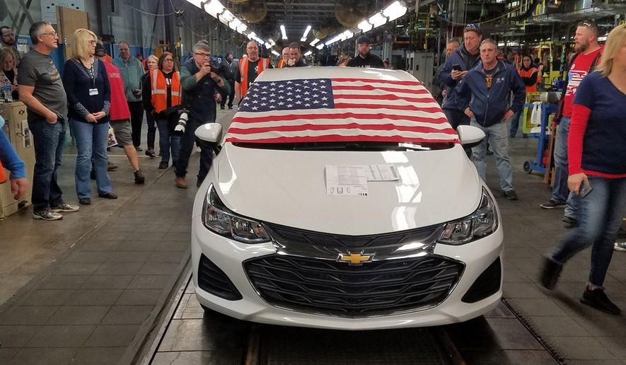 An American flag drapes the hood of the last Chevrolet Cruze as it comes off the assembly line at a General Motors plant where 1,700 hourly positions are being eliminated perhaps for good, on Wednesday, March 6, 2019, in Lordstown, Ohio. The factory near Youngstown is the first of five North American auto plants that GM plans to shut down by next year. (Tim O'Hara via AP)