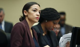 Rep. Alexandria Ocasio-Cortez, D-N.Y., left, looks over her notes during testimony by Michael Cohen, President Donald Trump's former lawyer, before the House Oversight and Reform Committee on Capitol Hill in Washington, Wednesday, Feb. 27, 2019. Sitting next to Ocasio-Cortez is Rep. Ayanna Pressley, D-Mass., right. (AP Photo/Pablo Martinez Monsivais)