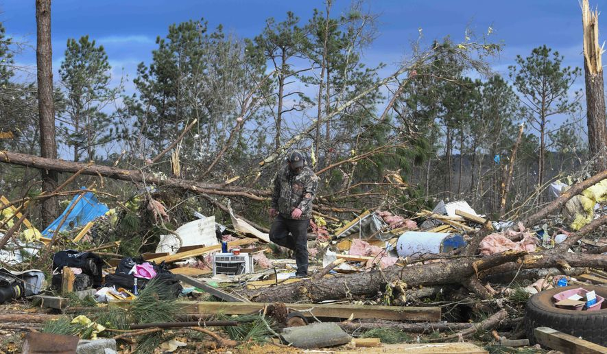 Residents and family members sift through the debris of their homes near Lee County Road 38 in Beauregard, Ala., Monday, March 4, 2019, a day after tornadoes ravaged the area. (AP Photo/Julie Bennett)