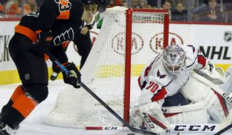 Philadelphia Flyers' Oskar Lindblom, left, digs at the puck blocked by Washington Capitals' Braden Holtby during the second period of an NHL hockey game Wednesday, March 6, 2019, in Philadelphia. The Capitols won 5-3. (AP Photo/Tom Mihalek) ** FILE **