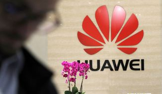 A logo of Huawei hangs in the lobby of the Cyber Security Lab at Huawei factory in Dongguan, China's Guangdong province, Wednesday, March 6, 2019. Huawei Technologies Co. is one of the world's biggest supplier of telecommunications equipment. (AP Photo/Kin Cheung)