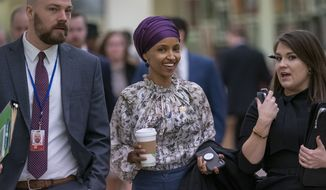 """Rep. Ilhan Omar, D-Minn., walks through an underground tunnel at the Capitol as top House Democrats plan to offer a measure that condemns anti-Semitism in the wake of controversial remarks by the freshman congresswoman, in Washington, Wednesday, March 6, 2019. Omar said last week that Israel's supporters are pushing U.S. lawmakers to take a pledge of """"allegiance to a foreign country."""" Despite criticism from Democrats and Republicans, Omar has refused to apologize. (AP Photo/J. Scott Applewhite)"""