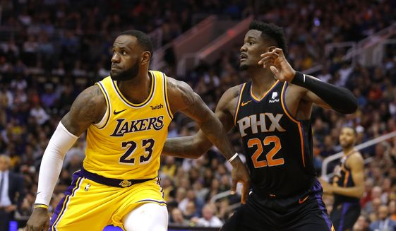 Los Angeles Lakers forward LeBron James (23) and Phoenix Suns center Deandre Ayton (22) in the first half during an NBA basketball game, Saturday, March 2, 2019, in Phoenix. (AP Photo/Rick Scuteri) **FILE**
