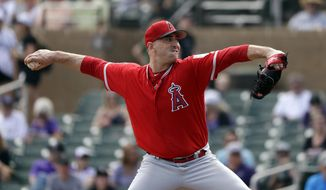 Los Angeles Angels starting pitcher Matt Harvey throws against the Colorado Rockies in the first inning of a spring training baseball game Wednesday, March 6, 2019, in Scottsdale, Ariz. (AP Photo/Elaine Thompson)