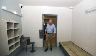 Australian Prime Minister Scott Morrison is seen inside a high care accommodation room as he tours North West Point Detention Centre on Christmas Island, Wednesday, March 6, 2019. Morrison says asylum seekers who are allowed to leave Pacific island migrant camps to get medical treatment in Australia will be sent to a prison-like facility on a remote island. (Lukas Coch/AAP Image via AP)