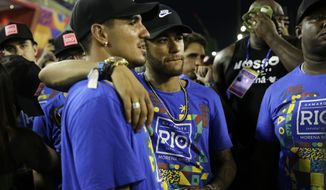 Brazil's soccer player Neymar, center, and surfer Gabriel Medina attend the Carnival celebrations at the Sambadrome in Rio de Janeiro, Brazil, Tuesday, March 5, 2019. (AP Photo/Silvia Izquierdo)